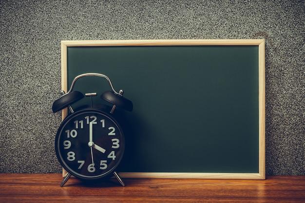 Черный винтажный будильник с зеленой доской, космос экземпляра для добавляет ваш текст, работает вовремя или с течением времени и концепцией крайнего срока.
