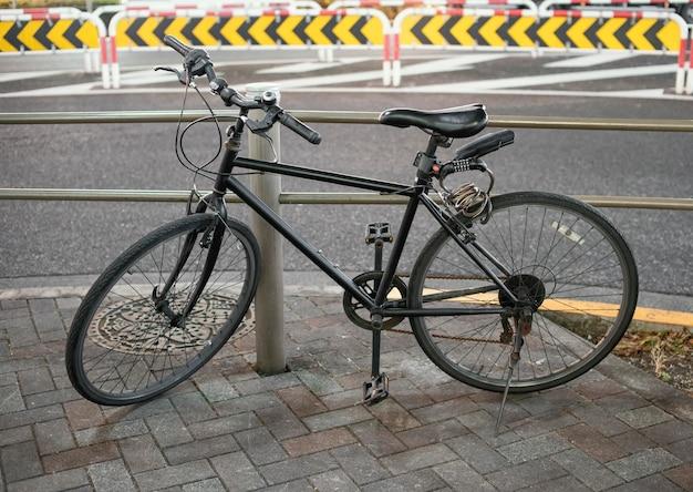 Black vintage bicycle parked on alley