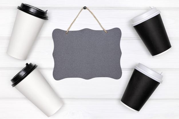 黒のヴィンテージ看板紙コーヒーカップ白塗りの木製ボードコーヒーのモックアップの背景に行く