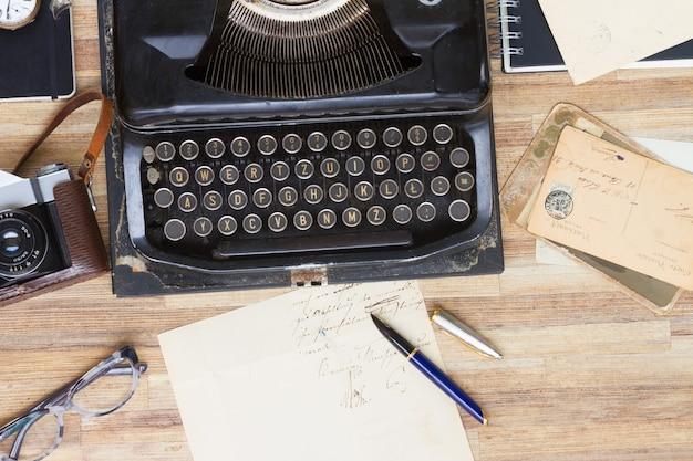 木製のテーブルに本と古いメールと黒のヴィンテージタイプライター
