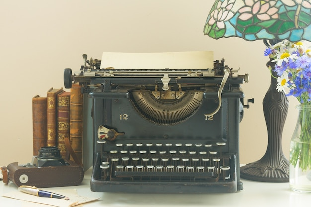 Black vintage typewriter with books on wooden table with art nuveau lamp close up