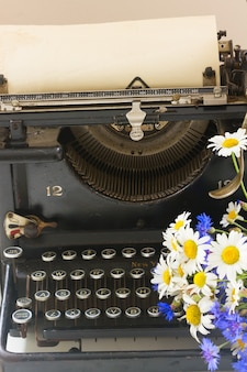Black vintage typewriter with books on wooden table with flowers close up