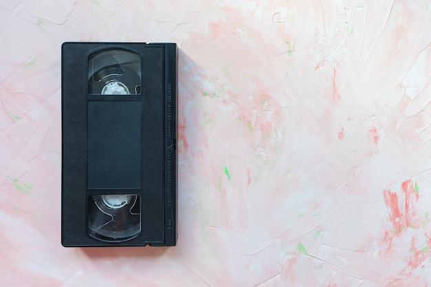 ピンクのレトロなミニマリストの背景に黒のヴィンテージvhsビデオテープ