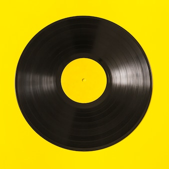 Black vinyl record on yellow background