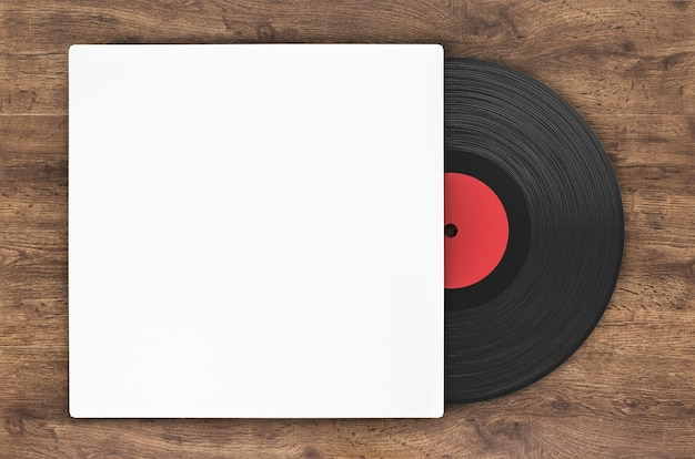 Black vinyl record in paper case on wood background