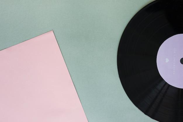 Черная виниловая пластинка с бумагой на столе