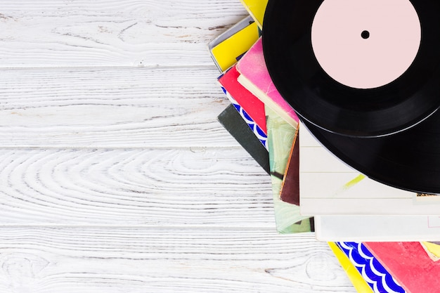 Black vinyl records on the wooden table, selective focus with copyspace. top view