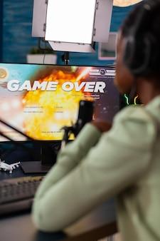 헤드폰으로 라이브 챔피언십을 잃는 블랙 비디오 게임 e스포츠 스트리머. 강력한 컴퓨터에서 새로운 그래픽으로 온라인 비디오 게임을 스트리밍하는 전문 게이머.