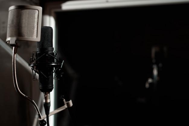 Черный вокальный микрофон стоит в студии звукозаписи