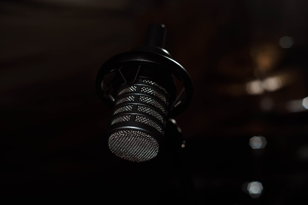 Black vocal microphone is stand in sound recording studio room using for podcast production radio or lead singer instrument meaning perform music audio wave