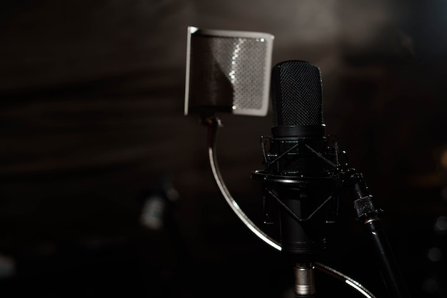 Black vocal microphone is stand in sound recording studio room