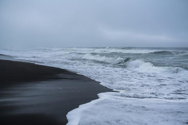 Черный вулканический песок на халактырском пляже тихого океана на камчатском полуострове, недалеко от петропавловска-камчатского, россия