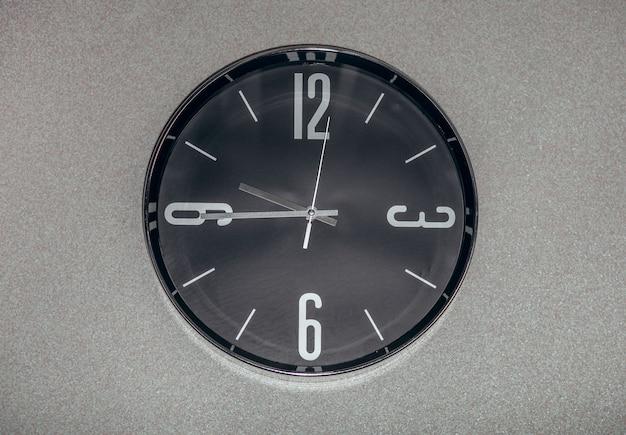 초침이 벽에 걸려있는 검은 벽 시계.