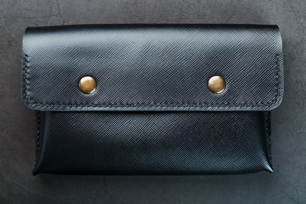 Black wallet made of genuine leather on dark