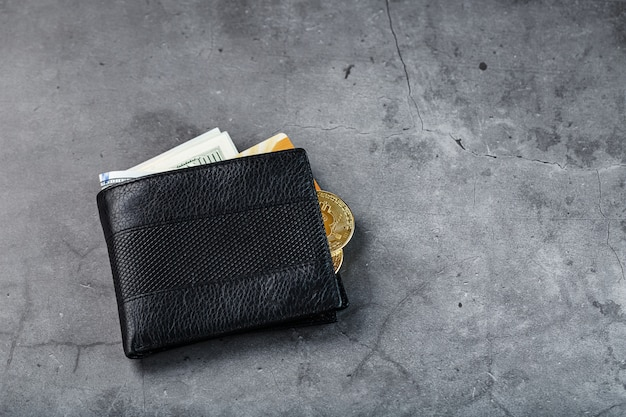 A black wallet with banknotes and a gold electronic card on a dark gray stone wall.