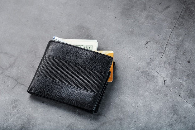A black wallet with banknotes and a gold electronic card on dark gray stone.