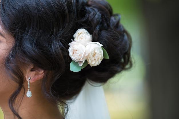 黒の結婚式のヘアスタイリング。髪留めと巻き毛のブルネットの花嫁。結婚式のコンセプト