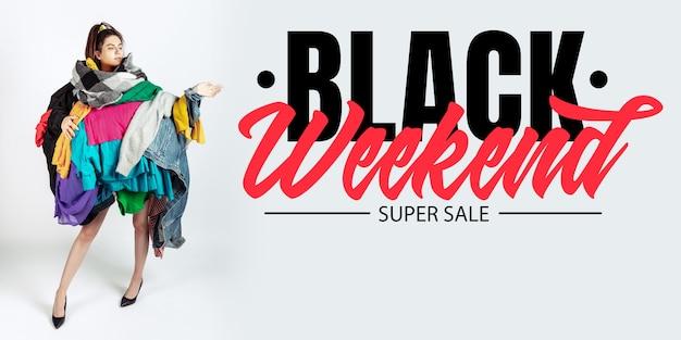 黒の週末、金融の概念。販売と服に夢中の女性。カラフルな服を着すぎた女性モデル。ファッション、スタイル、ブラックフライデー、セール、購入、お金、オンライン購入。広告のチラシ。