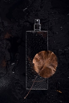 Black wet perfume on dark background