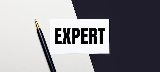 On a black and white background lies a pen and a white card with the text expert