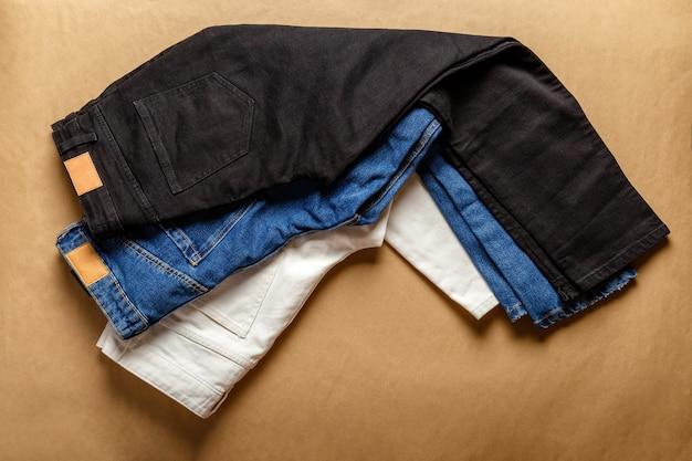 ブラックホワイトブルージーンズパンツ。 emtyラベル付きのストアショップでのさまざまな色のデニム服の品揃え。ホワイトデニムジーンズパンツ、ブルージーンズ、ブラウンテーブルにブラックデニム。