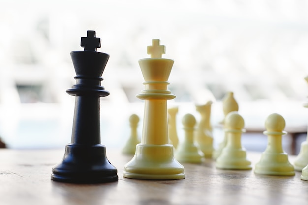 Black and white chess kings faced between defocused pieces on wooden board.