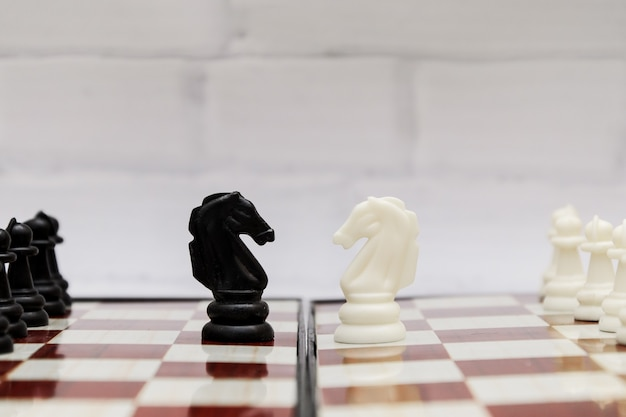 Black and white chess knights opposite each other on a chessboard