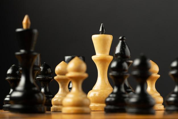Pezzi degli scacchi in bianco e nero su sfondo nero