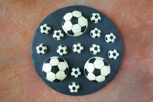 Black and white classic football balls on a black round serving plate - dessert cakes made of black and white milk chocolate on the field backgroung