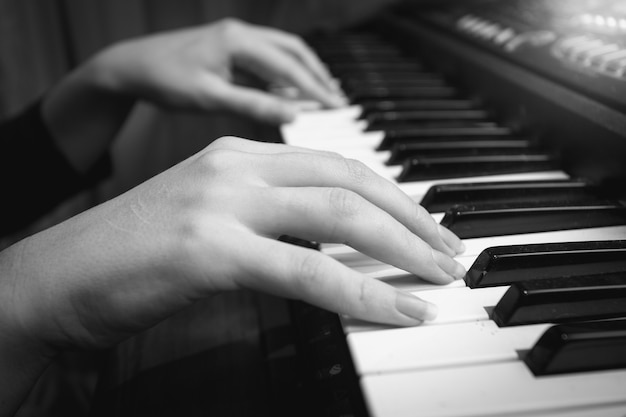 Black and white closeup photo of female hands on digital piano keyboard