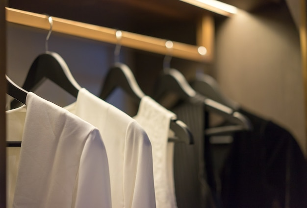 Black and white color tone clothes hanging on rail in a wardrobe, interior design.