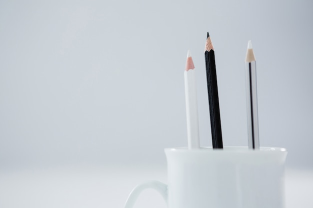 Black and white colored pencils kept in mug