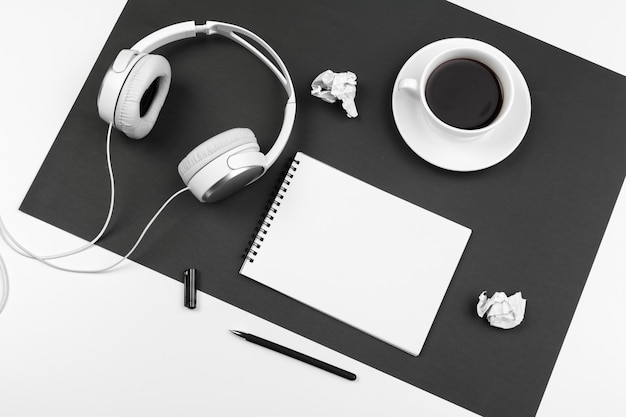 Black and white composition with stylish headphones, flat lay