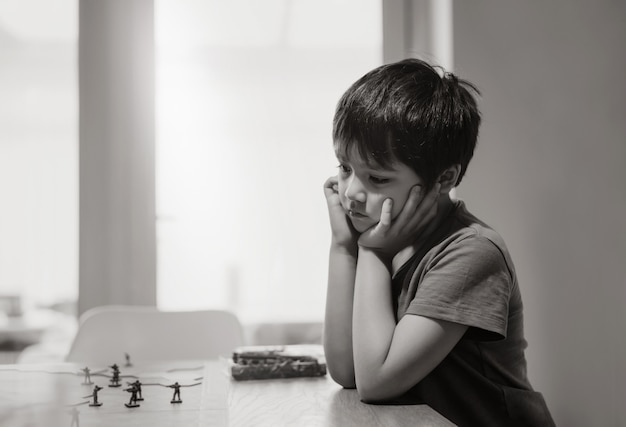 Black and white emotional portrait of sad kid sitting alone and playing with tank toys