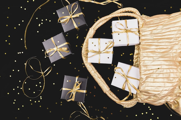 Black and white gift boxes with gold ribbon pop out from golden bag on shine. flat lay