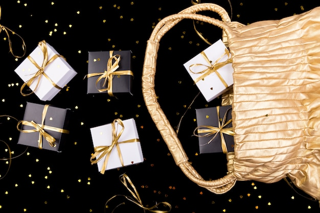 Black and white gift boxes with gold ribbon pop out from golden bag on shine surface,