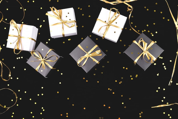 Black and white gift boxes with gold ribbon on shine. flat lay.