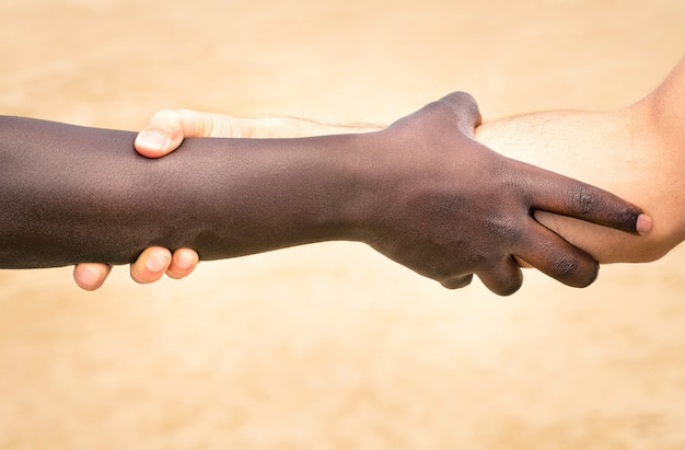 Black and white hands in modern handshake to show each other friendship and respect