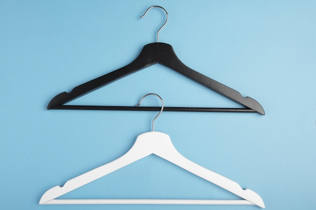 Black and white hangers interlocked with each other on blue. concept view.