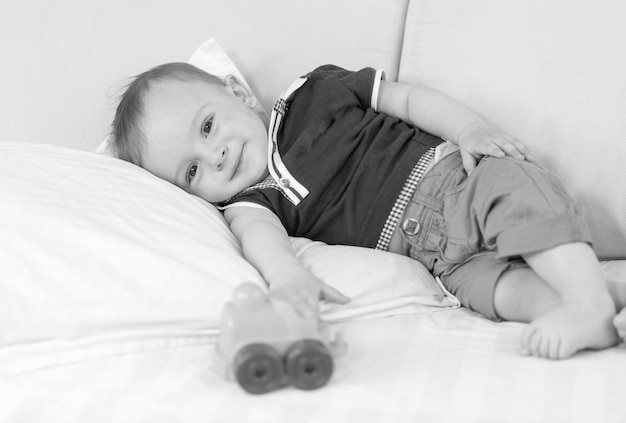 Black and white image of 1 year old baby boy resting on bed after playing with toys