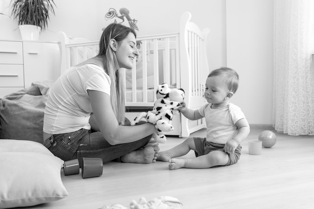 Black and white image of beautiful young mother and her 10 months old baby son playing with puppets on floor