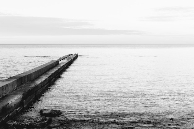 Black and white image of a concrete pier on the coast