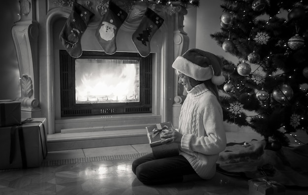 Black and white image of girl holding gift box and sitting next fireplace and decorated christmas tree