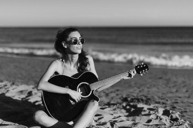 Black and white image of girl playing guitar at the beach
