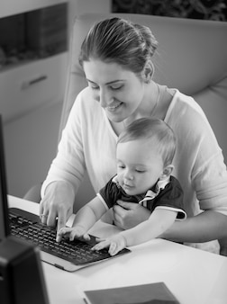 Black and white image of little baby boy sitting on mothers lap and using keyboard