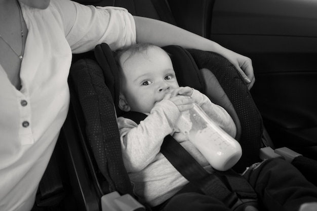 Black and white image of mother feeding baby from bottle in car