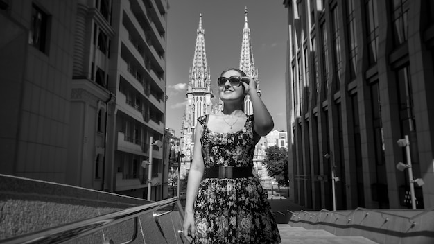 Black and white image of smiling young woman in sunglasses walking on street with modern building and ancient cathedrals