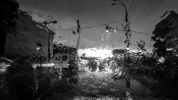 Black and white image of water droplets flowing on car windscreen while raining. wet automobile windscreen