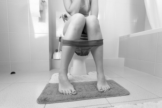 Black and white image of young woman sitting on toilet with red lace panties pulled down