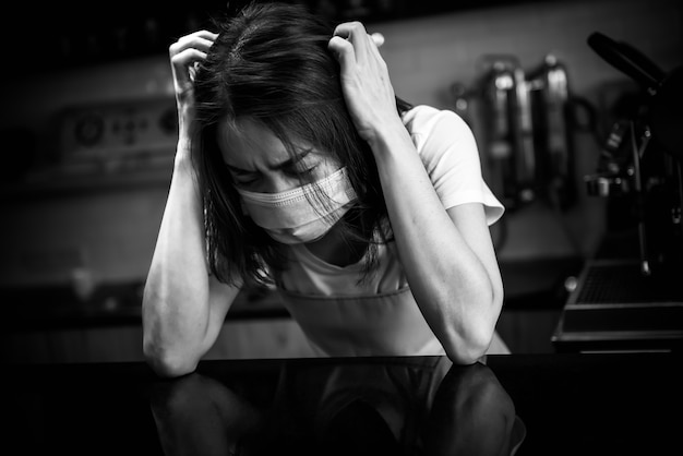 Black and white images of woman wear a surgical mask she is stressed and upset